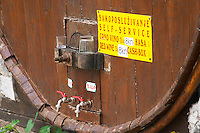 A big barrel at a winery for self service buying the wine. Two taps for red and white and a glass to taste. One tap for red and one for white. Put 8 kn in the box. Potmje village, Dingac wine region, Peljesac peninsula. Dingac village and region. Peljesac peninsula. Dalmatian Coast, Croatia, Europe.