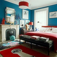 "A Fornasetti-inspired rug is one of the bright red accents in the master bedroom which is painted a deep ""Caribbean"" blue; the bench at the end of the bed is an Anthony Todd design"