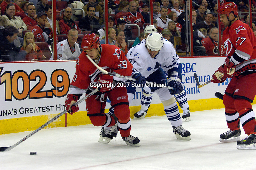 Toronto Maple Leafs' Pavel Kubina (31) and the Carolina Hurricanes' Chad LaRose (59) battle for a puck Tuesday, Jan. 30, 2007 at the RBC Center in Raleigh. The Leafs won 4-1.