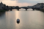 Boat on the river Arno at dusk, Florence, Italy.