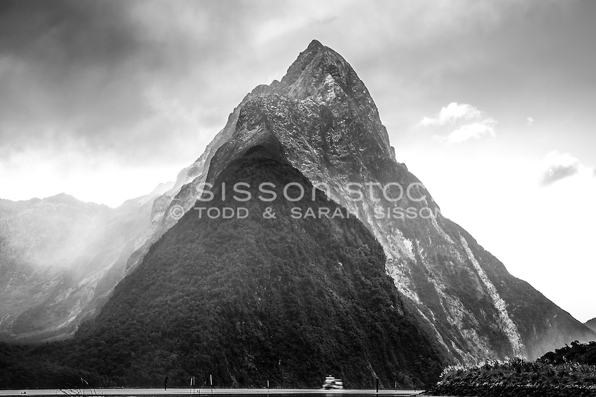 Close up portrait of Mitre Peak (in black and white), surrounded by cloud, with small cruise boat dwarfed in the foreground, Milford Sound, Fiordland National Park, South Island, New Zealalnd- stock photo, canvas, fine art print