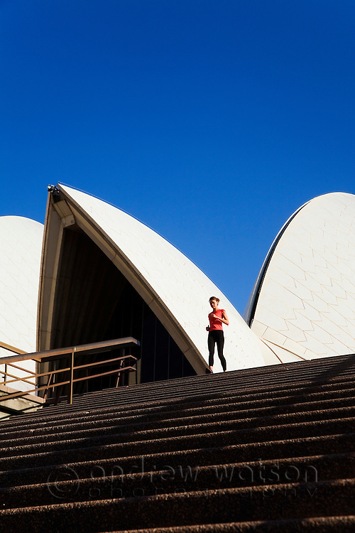 A woman runs down the steps of the Sydney Opera House. Sydney, New South Wales, AUSTRALIA.