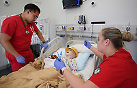 NWA Democrat-Gazette/DAVID GOTTSCHALK Steve Franco (left) and Miranda Lambert, both seniors at the University of Arkansas and first semester students in the Eleanor Mann School of Nursing, work with a pediatric simulator Thursday, February 22, 2018, in the Eppley Center of Health Professions on the campus in Fayetteville. A large demand for nurses continues to exist in northwest Arkansas.