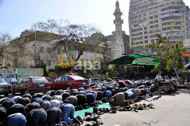 """Egyptian protesters pray outside the Mustafa Mahmoud Mosque before a demonstration calling for Islamist President Mohamed Morsi to step down, in Cairo on February 8, 2013. Thousands took to the streets after opposition groups called for """"Friday of dignity"""" rallies demanding Egyptian President Mohamed Morsi fulfill the goals of the revolt that brought him to power. Photo by Tarek al-Gabas"""