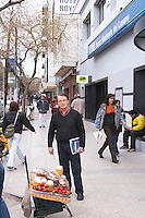 A street merchant selling strawberries and a man watching on the pavement Neuquen, Patagonia, Argentina, South America