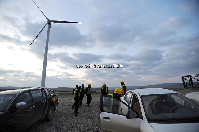 Portuguese workers stretch before getting to work just after dawn at a four windmill windfarm under construction being built by the Spanish firm Gamesa which will exclusively power the nearby Caspian Fisheries, a caviar company and packaging plant, when completed in late 2011 or early 2012, near Xirdalan, Azerbaijan on December 5, 2011.  Traditionally an oil and gas rich and reliant country, this wind farm is among the first wind farms to be built in Azerbaijan.
