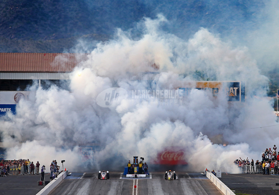 Feb 21, 2015; Chandler, AZ, USA; Smoke fills the air as a pair of jet dragster launch off the starting line following NHRA qualifying for the Carquest Nationals at Wild Horse Pass Motorsports Park. Mandatory Credit: Mark J. Rebilas-
