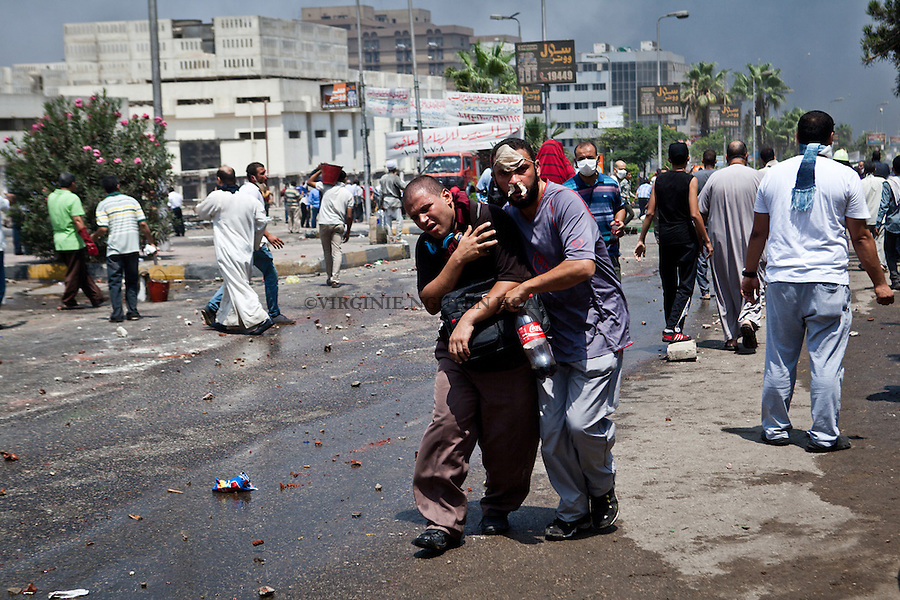 Un manifestant porte un homme blessé lors d'affrontements avec la police dans la rue Tayaran près de Rabaa square, Nasr city, Le Caire, Egypte, le mercredi 14 août 2013.