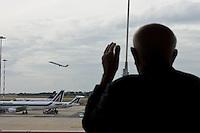 Un anziano signore osserva un aereo decollare dall'aeroporto Leonardo da Vinci di Roma