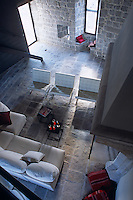 A row of cream leather Mies van der Rohe Barcelona chairs stand by the large stone fireplace