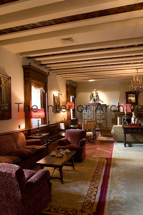 The main salon serves as a lobby for the Parador hotel, Hostal dos Reis Catolicos, and is furnished with plush velour seating and a collection of antique religious art.