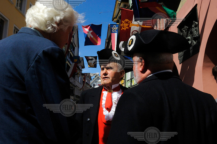 Appenzeller men, some in traditional costume, in discussion prior to going to vote in the annual Landsgemeinde (Cantonal Assembly), where regional issues are voted on in the main square by a show of hands. Appenzell is a distinctly traditional canton, one of the last remaining places where this direct form of democracy - in which there is no anonymity - is still used, and where women only received the right to vote in 1990. Men carry swords as symbols of their right to vote.