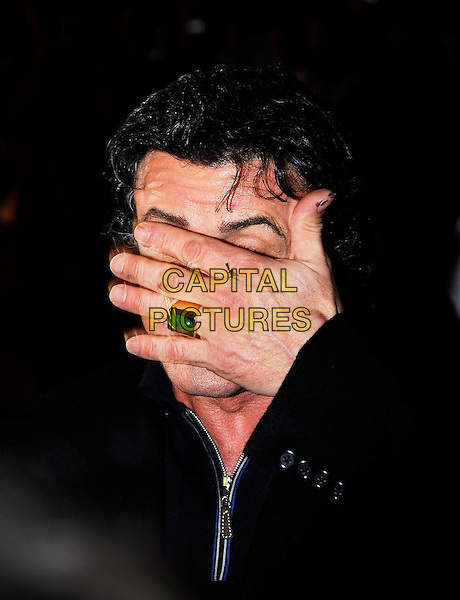 "SYLVESTER ""SLY"" STALLONE.At the UK Film Premiere of ""Rocky Balboa"", .Vue West End Cinema, London, England,.January 16th 2007..portrait headshot hand over face green stone ring hiding.CAP/IA.©Ian Allis/Capital Pictures"