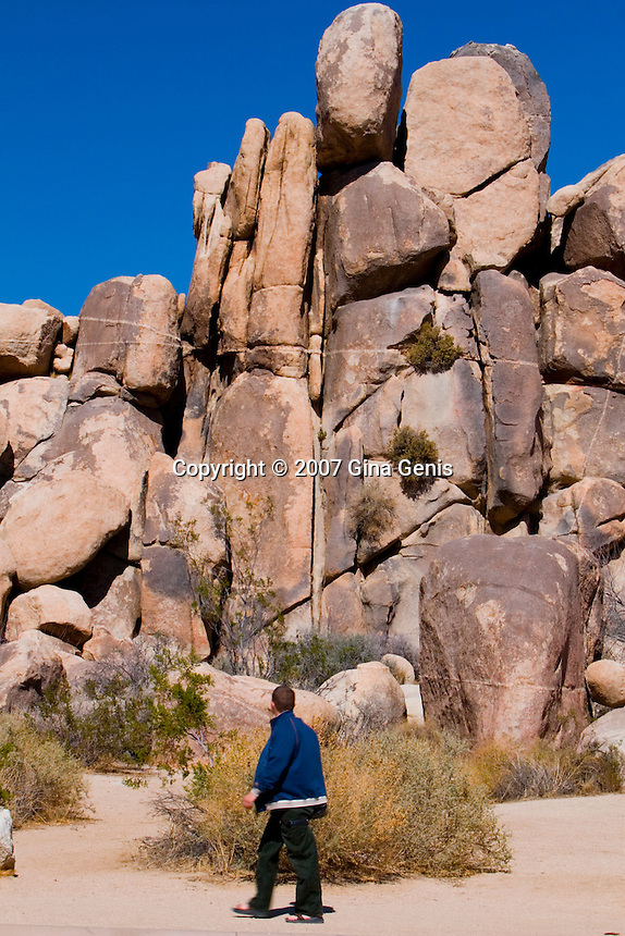 Man at the base of a rock formation in Joshua Tree National Park