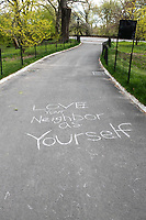 New York, New York City, during the time of the Coronavirus. Love Your Neighbor As Yourself written in chalk in Central Park.