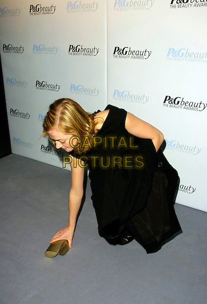 CAMILLA RUTHERFORD.P&G Beauty Awards, Hayward Gallery, South Bank, London, UK..February 1st, 2007.full length black coat dress gold clutch purse bending over leaning picking up off floor.CAP/CAN.©Can Nguyen/Capital Pictures