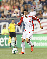 Toronto FC midfielder Jonathan Osorio (21) brings the ball forward.  In a Major League Soccer (MLS) match, Toronto FC (white/red) defeated the New England Revolution (blue), 1-0, at Gillette Stadium on August 4, 2013.