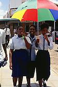 Victoria Falls, Zambia. Three smiling happy schoolgirls in school uniform, one carrying a multicoloured umbrella sunshade.