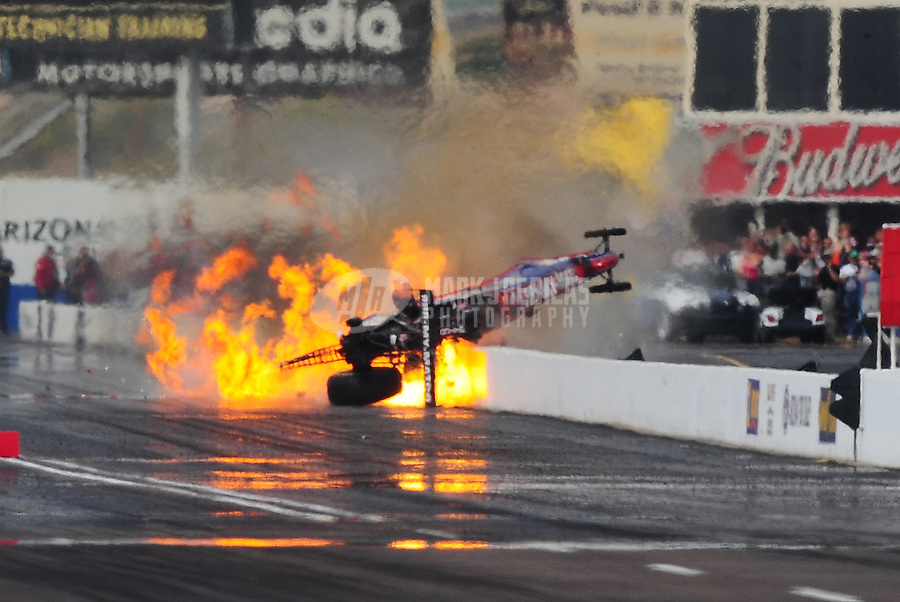 Feb. 21, 2010; Chandler, AZ, USA; NHRA top fuel dragster driver Antron Brown bursts into flames as he crashes during the Arizona Nationals at Firebird International Raceway. A tire from his car flew over the trackside wall and into a spectator area causing serious injuries. Mandatory Credit: Mark J. Rebilas-