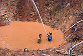Maria Bonita, Xingu, Brazil. Garimpo illegal gold mine with garimpeiros in muddy water using high pressure hose.