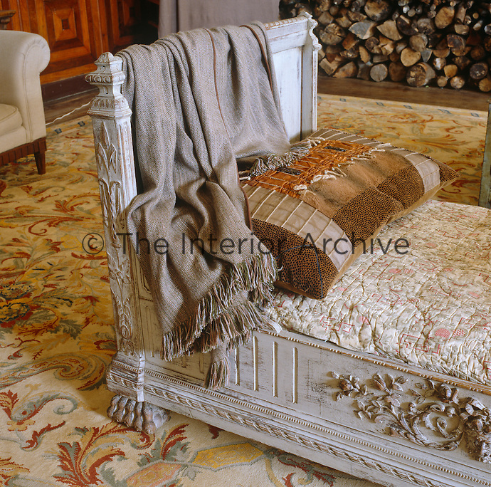 Detail of a French wooden daybed draped in a grey shawl which stands in the centre of the living room
