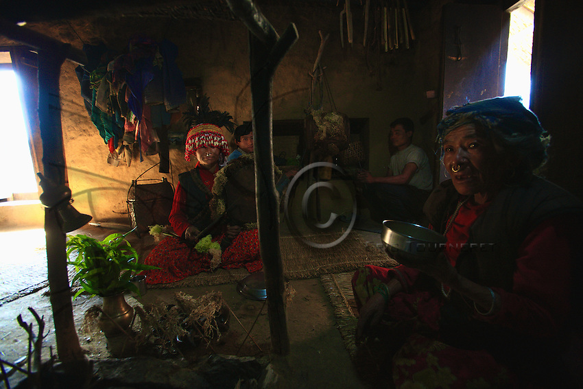 """This woman shaman has taken over the duties of the """"mop,"""" her husband, now too old to officiate. The sacred drum helps her achieve a trance state to communicate with the spirit world."""