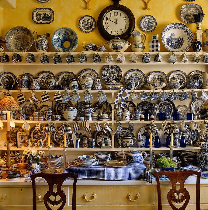 The shelves and surfaces of this dresser are filled with a large collection of blue and white china