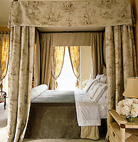 A black-lacquered and faded gold leaf four-poster bed is draped with taupe toile curtains and a long, soft bedcover