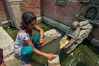 Nepal, Kathmandu, people lined up with water containers at the fountain for water Durbar Square. Women filling containers.