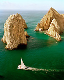 MEXICO, Cabo San Lucas, Baja, a catamaran sailing by the archway at Lover's Beach, also known as Land's End