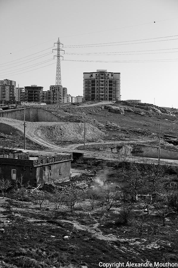 La croissance urbaine de la ville nouvelle de Mardin: au premier plan une maison de campagne voit la ville se rapprocher.