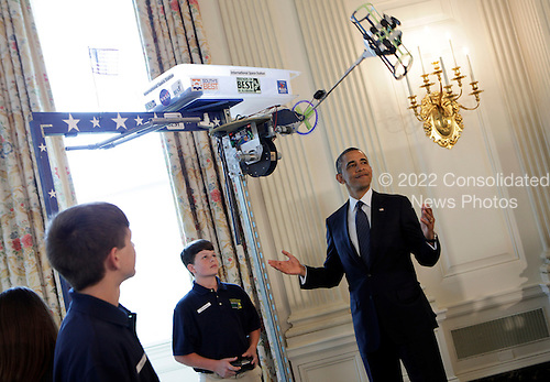 United States President Barack Obama  looks at the Robot &quot;Vator&quot; created and presented by Victoria Flechter, Rush Lyons, and Thomas Shields from St Vincent de Paul, Theodore Alabama in the State Dining Room of the White House in Washington, D.C. during the  White House Science Fair on April 22, 2013. It mimic space space elevators by carrying cargo up a 10 foot pole.The White House Science Fair celebrates the student winners of a broad range of science, technology, engineering and math (STEM) competitions from across the country. The first White House Science Fair was held in late 2010.<br /> Credit: Aude Guerrucci / Pool via CNP