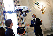 """United States President Barack Obama  looks at the Robot """"Vator"""" created and presented by Victoria Flechter, Rush Lyons, and Thomas Shields from St Vincent de Paul, Theodore Alabama in the State Dining Room of the White House in Washington, D.C. during the  White House Science Fair on April 22, 2013. It mimic space space elevators by carrying cargo up a 10 foot pole.The White House Science Fair celebrates the student winners of a broad range of science, technology, engineering and math (STEM) competitions from across the country. The first White House Science Fair was held in late 2010.<br /> Credit: Aude Guerrucci / Pool via CNP"""