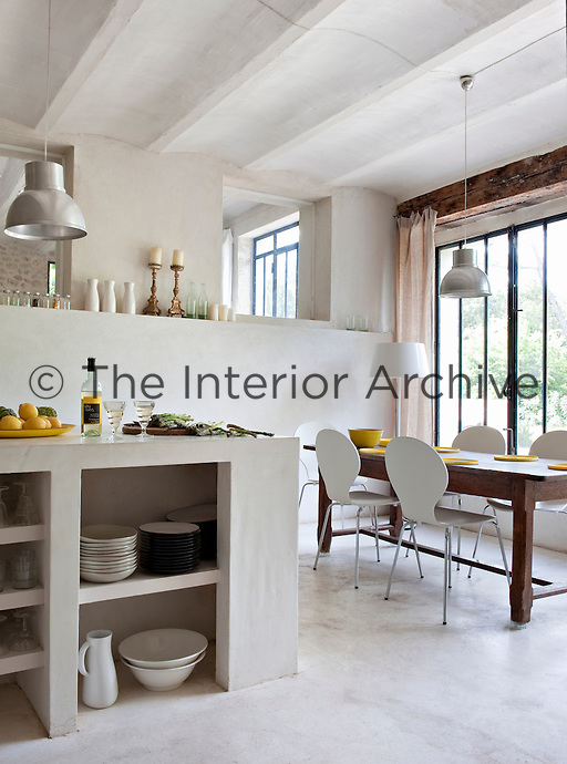 In the kitchen there is plenty of room for the large antique table surrounded by contemporary chairs whilst natural light streams in via the bespoke metal windows fabricated by Jules Terras