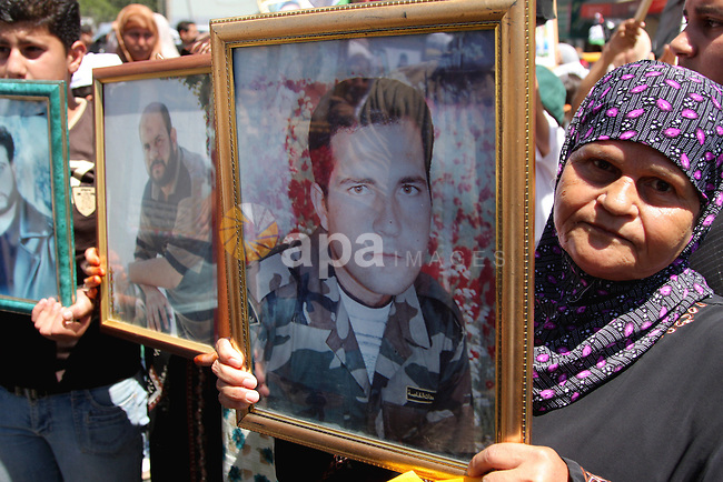A Palestinians hold their relatives pictures and their national flag during a rally calling for release their relatives who held in Israeli jails in the West Bank of Ramallah on July 28, 2009. Photo by Issam Rimawi