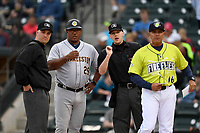 Manager Pedro Lopez (16) of the Columbia Fireflies, right, confers with umpire Chris Silvestri, Charleston manager Julio Mosquera and umpire Matt Baldwin before a game against the Charleston RiverDogs on Thursday, April 4, 2019, at Segra Park in Columbia, South Carolina. Charleston won, 2-1. (Tom Priddy/Four Seam Images)