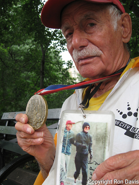 """Alberto Arroyo was known as """"the Mayor of Central Park for 70 years"""". He was awarded the prestigious Medal For Overcoming Adversity. This photo was taken in Central Park, NYC, June '06.  Mr. Arroyo passed away in 2010 at the age of 94 years. A former boxer from Puerto Rico, Arroyo had taken to running in Central Park along the bridle path, but after a police officer told him he was bothering the horses, Arroyo ran around the reservoir. That was 1937. Arroyo also used to run during his lunch hour while working at Bethlehem Steel in Battery Park, which was unheard of back then, and ran in the first NYC marathon. In more recent years, Arroyo would walk clockwise around the reservoir with a walker, greeting runners and offering them encouragement. He was even given a State Senate resolution in 1985, acknowledging his 50 years of running and calling him one of the """"pioneers of the jogging trend."""""""