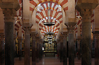 The hypostyle prayer hall, area built in the 10th century under Al-Mansur, 987-988, in the Cathedral-Great Mosque of Cordoba, in Cordoba, Andalusia, Southern Spain. The hall is filled with rows of columns topped with double arches, a horseshoe arch below a Roman arch, in stripes of red brick and white stone. Behind is one of the cathedral chapels. The first church built here by the Visigoths in the 7th century was split in half by the Moors, becoming half church, half mosque. In 784, the Great Mosque of Cordoba was begun in its place and developed over 200 years, but in 1236 it was converted into a catholic church, with a Renaissance cathedral nave built in the 16th century. The historic centre of Cordoba is listed as a UNESCO World Heritage Site. Picture by Manuel Cohen