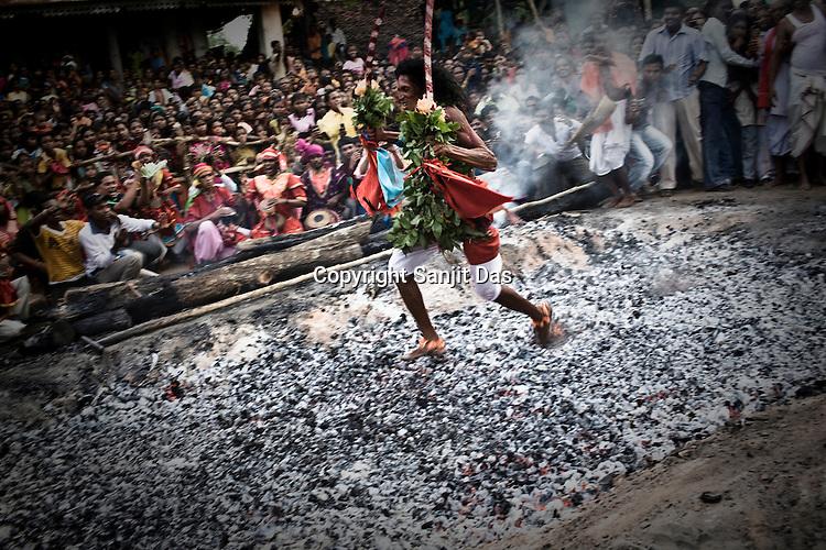 A religious Kondh tribesman runs over burning coals during an annual festival in Lanjigarh, Orissa, India.
