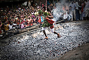 A religious Kondh tribesman runs over burning coals during an annual festival in Lanjigarh, Orissa, India.
