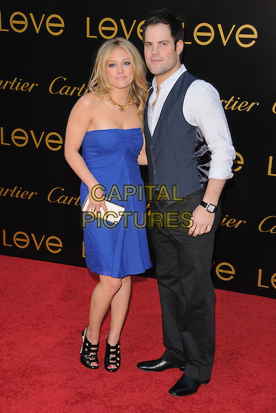 HILARY DUFF & MIKE COMRIE .The 3rd Annual Leveday Hosted by Cartier held at a private estate in Bel Air, California, USA..June 18th, 2008.full length black strappy straps buckles gold studs heels sling back blue strapless dress white clutch bag waistcoat trousers couple .CAP/DVS.©Debbie VanStory/Capital Pictures.