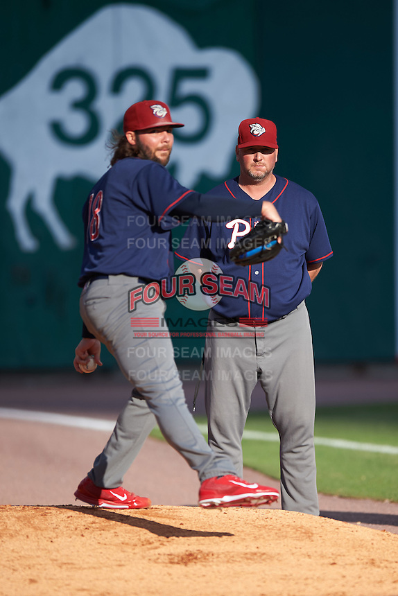 Lehigh Valley IronPigs pitching coach David Lundquist (34) watches starting pitcher James Russell (18) warm up before a game against the Buffalo Bisons on July 9, 2016 at Coca-Cola Field in Buffalo, New York.  Lehigh Valley defeated Buffalo 9-1 in a rain shortened game.  (Mike Janes/Four Seam Images)