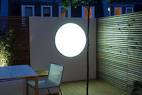 Dusk view out onto the tiny decked garden seating area. A light feature provides focus to the overall design.