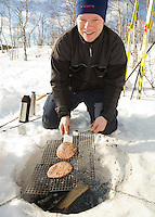 Sweden, SWE, Kiruna, 2006-Apr-16: Barbecue party in Lapland: a man is sitting on the banks of the frozen Holmajarvi lake and frying hamburgers on an open fire.