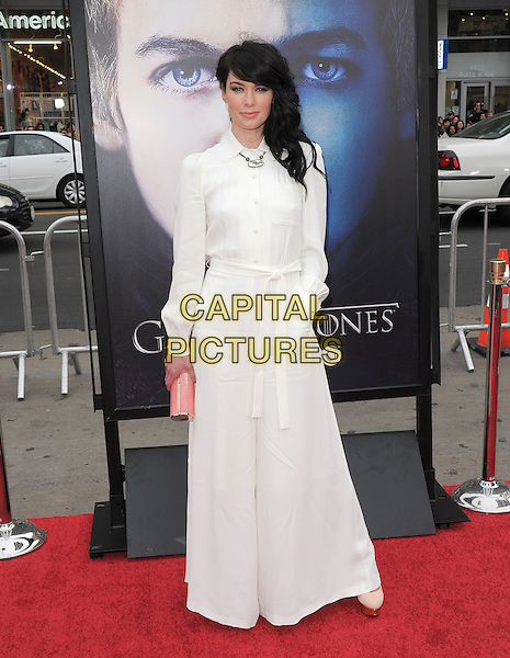 """Lena Headey.""""Game Of Thrones"""" 3rd Season Los Angeles Premiere held at the TCL Chinese Theatre, Hollywood, California, USA..March 18th, 2013.full length white jumpsuit knotted sash belt waist flared wide leg trousers pink clutch bag hand in pocket .CAP/RKE/DVS.©DVS/RockinExposures/Capital Pictures."""