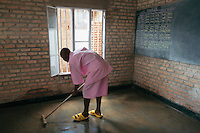 Rwanda. Southern province. District of Muhanga. Central jail of Gitarama. Minors block. A teenager boy, wearing the pink prisoner's clothes and yellow plastic shoes, cleans the floor of the classroom. Bricks wall and a barred window. Behind bars. Minors in detention behind bars. Detention pending trial and after trial, when sentenced to prison. The non-governmental organization (NGO) Fondation DiDé - Dignité en détention runs the Encademi (Encadrement des mineurs) program. Prison centrale de Gitarama. Quartier des mineurs.  © 2007 Didier Ruef