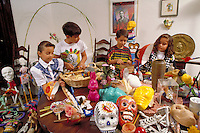 HISPANIC CHILDREN AT HOME PREPARING ALTAR FOR DAY OF THE DEAD CELEBRATION. HISPANIC FAMILY. SACRAMENTO CALIFORNIA.