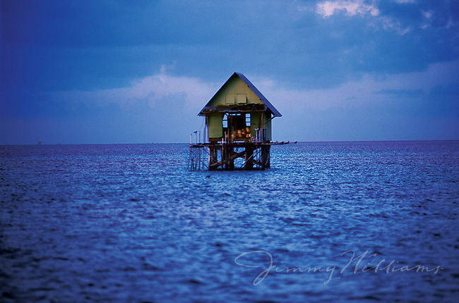 A small fishing shack sits in the middle of the ocean off the shore of Tahiti