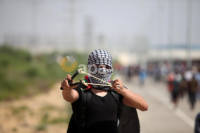 A Palestinian protester uses a sling shot to throw stones during clashes with Israeli security forces next to the border fence with Israel, at the Erez crossing in the northern Gaza strip, on October 13, 2015. A wave of stabbings that hit Israel, Jerusalem and the West Bank this month along with violent protests in annexed east Jerusalem and the occupied West Bank, has led to warnings that a full-scale Palestinian uprising, or third intifada, could erupt. The unrest has also spread to the Gaza Strip, with clashes along the border in recent days leaving nine Palestinians dead from Israeli fire. Photo by Ashraf Amra