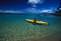 Girl heads out with yellow kayak through clear water at Napili Bay, Maui.
